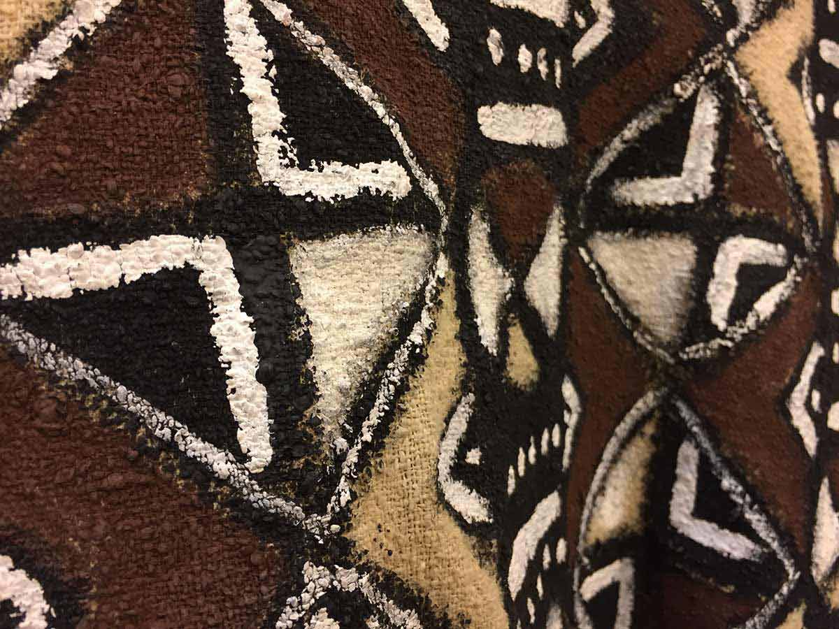 The wardrobe crew hand painted Athena's shirt to replicated traditional mud cloth from Mali.
